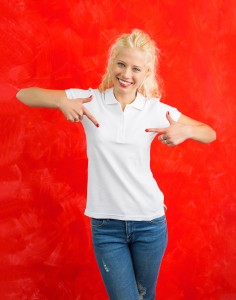 Woman in white polo T-shirs on red background pointing at it wit